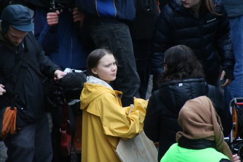 Greta Thunberg stands in crowd with her iconic mustard yellow waterproof